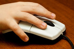 Children's hand on computer mouse Royalty Free Stock Images