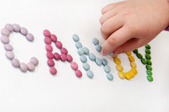 Children's hand creates a sign of colorful chocolate candies Stock Photos