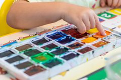 Children`s hand dips a finger into the paint on the palette to draw. A picture stock photo