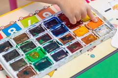 Children`s hand dips a finger into the paint on the palette to draw. A picture stock images