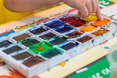 Children& x27;s hand dips a finger into the paint on the palette to draw. A picture royalty free stock image