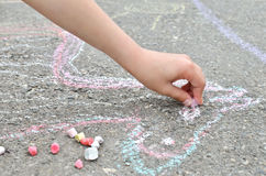 Children's hand draws with chalk on the pavement. Creative leisure Stock Photo