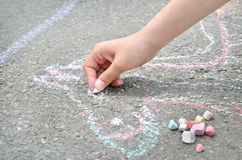 Children's hand draws with chalk on the pavement. Creative leisure Royalty Free Stock Photo