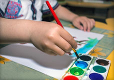 Children's hand draws paints. On a sheet of paper Royalty Free Stock Photos