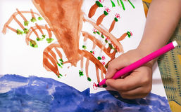 Children's hand draws pink flowers on a tree. Children's hand draws a pink flower on a tree-tip pen Stock Photos