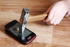 Children`s hand with a hammer breaks the smartphone, object royalty free stock photo