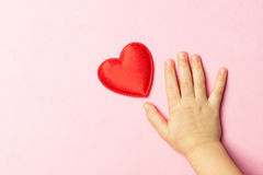 Children`s hand and heart. Children`s hand near the heart on a pink background. Concept of love, care, faith, hope, purity. Place for text. Flat fly Stock Images