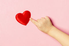Children`s hand and heart. Children`s hand pointing at the heart on a pink background. Concept of love, care, faith, hope, purity. Place for text. Flat fly Royalty Free Stock Images
