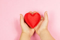 Children`s hand and heart. Children`s hands holding the heart on a pink background. Concept of love, care, faith, hope, purity. Place for text. Flat fly Royalty Free Stock Photos