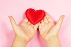 Children`s hand and heart. Children`s hands holding the heart on a pink background. Concept of love, care, faith, hope, purity. Place for text. Flat fly Stock Images