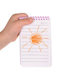 Children's hand hold notebook with a painted sun Royalty Free Stock Image