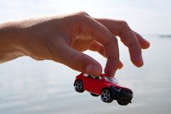 Children`s Hand Holding A Red Car Over The Roof Over The Sea Water Gray, Summer Day During Royalty Free Stock Photos
