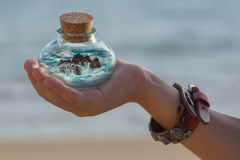 Children`s hand holding a bottle with the ocean and rocks inside. Children`s hand holds a bottle with a cork with the ocean waves and rocks inside Stock Images