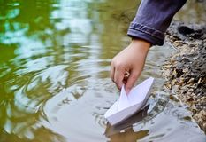 Children`s hand let the paper boat. In a puddle Stock Photo