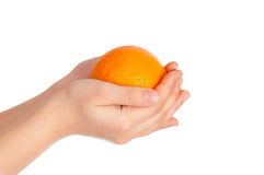 Children's hand with an orange on white Royalty Free Stock Photography