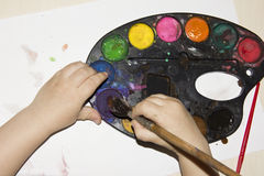 Children's hand in the paint top view royalty free stock photography