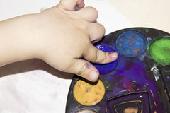 Children's hand in the paint top view stock photo