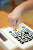 Children`s hand presses on button calculator. Children`s hand presses off red button calculator Stock Photo