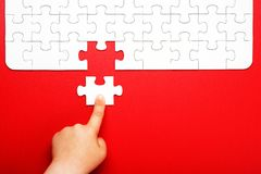 Children`s hand moves a piece of white puzzle on a red background. Children`s hand puzzle white piece on a red background. Business and teamwork and society royalty free stock photos