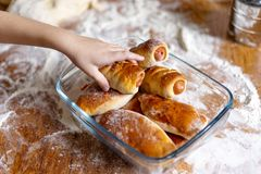 Children`s hand reaches for a homemade bun royalty free stock images