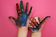 Children`s hand, smeared with multicolored paint on a pink background. Thumbs up stock image