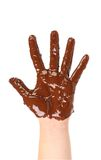 Children's hand stained with chocolate frosting. Stock Image