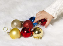 Children's hand taking Christmas tree decorations Royalty Free Stock Photos