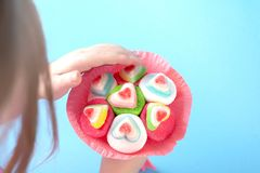 Children`s hand touches a bouquet of marmalade and sweets in a pink box on a turquoise background stock photo