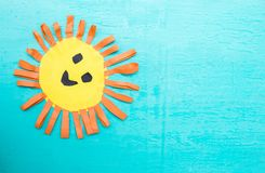 Children`s handmade from colored paper - the sun with a smile. On blue background Stock Images