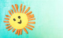 Children`s handmade from colored paper - the sun with a smile. On blue background Stock Photos