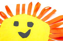 Children`s handmade from colored paper - the sun with a smile. Isolated on white background Stock Image