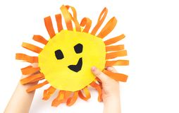 Children`s handmade in hands from colored paper - the sun with a smile. Isolated on white background Royalty Free Stock Photos