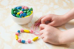 Children's hands collect beads on a string. Children's hands to collect different colored wooden beads on a string royalty free stock photos