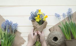 Children`s hands collect a bouquet as a gift. A gift for mom. Spring festive bouquet in a crafting package. Pruning flowers. The child is a florist. Wooden stock images
