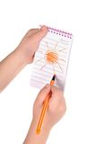 Children's hands hold notebook with a painted sun royalty free stock image