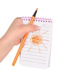 Children's hands hold notebook with a painted sun Stock Image