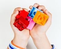 Children`s hands hold parts of Lego.  royalty free stock photography