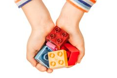 Children`s hands hold parts of Lego.  royalty free stock image