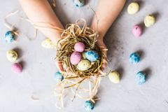 Children`s hands holding colorful easter eggs which lying in nest. Flat lay. Top view. Holiday concept stock images