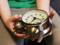 Children`s hands holding a gold alarm clock stock image