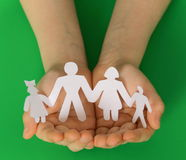 Children's hands holding a paper family Royalty Free Stock Photo