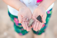 Children`s hands holding wet pebble and sea conch shell on the beach by the sea. Happy children`s play outdoor in summer. Love f stock photo