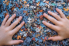 Children`s hands on Jigsaw puzzle color background Royalty Free Stock Images