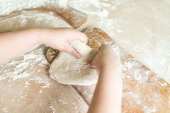 Children`s hands make dough. Side view shoot of children`s hands make dough on the wooden board. Learning in kindergarten royalty free stock images