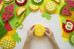 Children`s hands make fruit from paper. Tropics summer. Master class from the child. Royalty Free Stock Photo