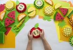 Children`s hands make fruit from paper. Tropics summer. Master class from the child. Royalty Free Stock Image