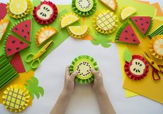 Children`s hands make fruit from paper. Tropics summer. Master class from the child. Stock Photo