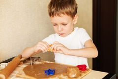 Children`s hands make gingerbread. Small boy cutting cookies for Stock Image