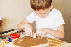 Children`s hands make gingerbread. Small boy cutting cookies for Stock Photo