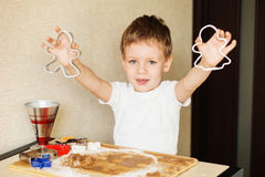 Children`s hands make gingerbread. Small boy cutting cookies for Royalty Free Stock Images